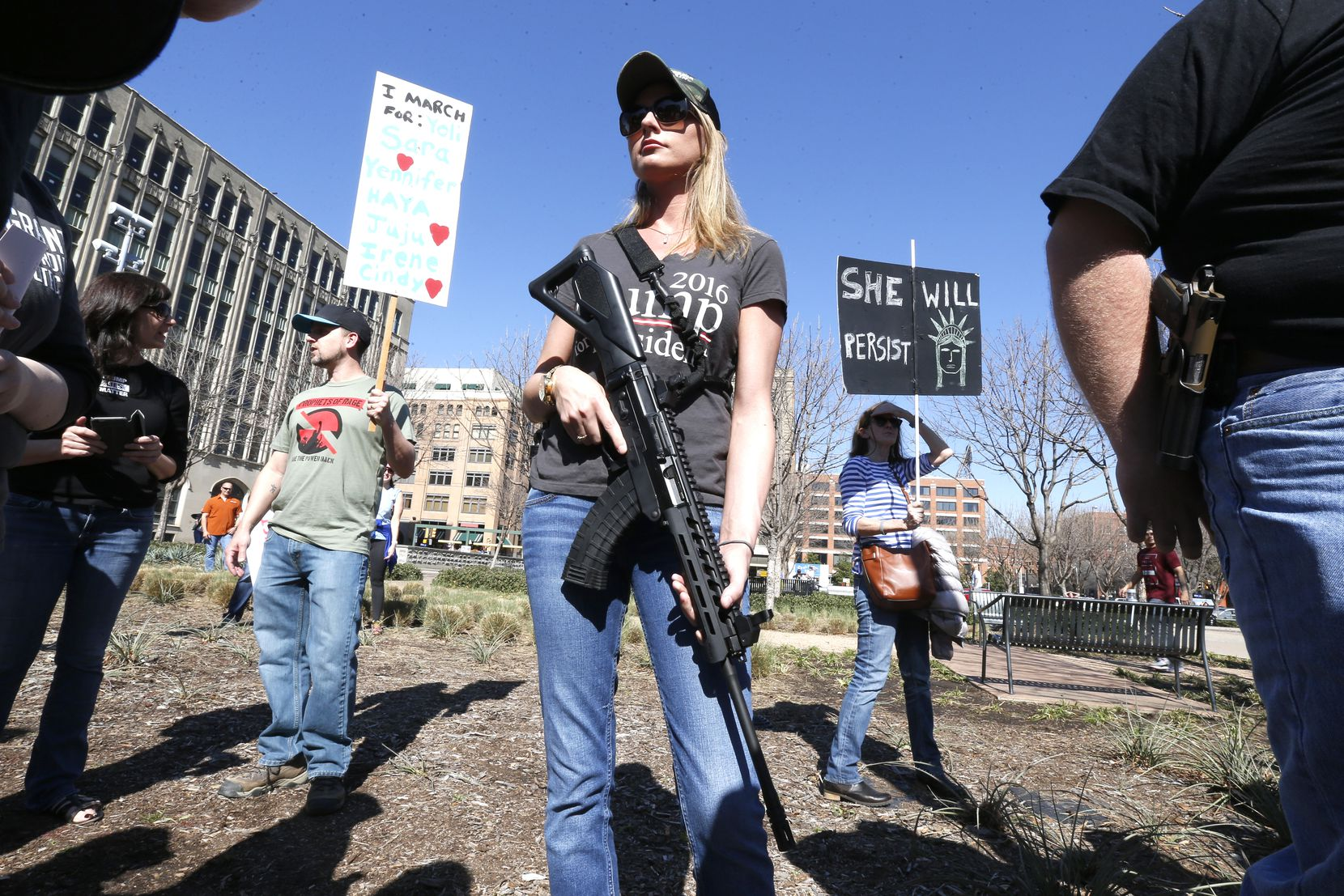 Brooke Wang, of Plano, Texas open carries a rifle while joining a very small group of counterprotesters, as hundreds rallied nearby in support of immigrant and refugee communities in downtown Dallas on February 18, 2017. (Nathan Hunsinger/The Dallas Morning News)