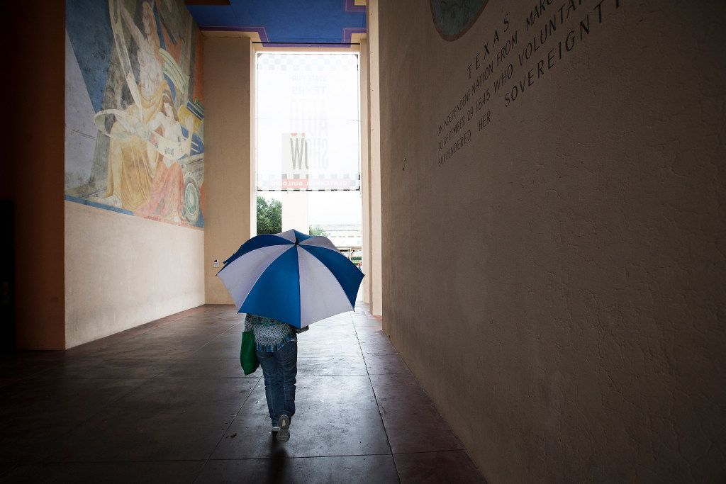A fairgoer takes cover under an umbrella as rain falls during the State Fair of Texas at Fair Park on Friday, Oct. 14, 2016, in Dallas. (Smiley N. Pool/The Dallas Morning News)