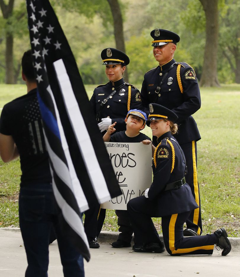 Jayden Morales of Grand Prairie, Texas has his photo made with members of the Dallas Police Department before the burial of fellow police officer Rogelio Santander, Jr.