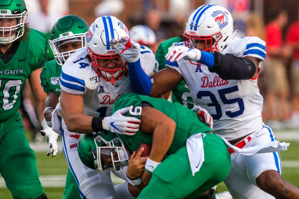 UNT quarterback Mason Fine (6) is sacked by SMU linebacker Richard Moore (14) and defensive end Delontae Scott (35) during the first half of an NCAA football game at Ford Stadium on Saturday, Sept. 7, 2019, in Dallas.