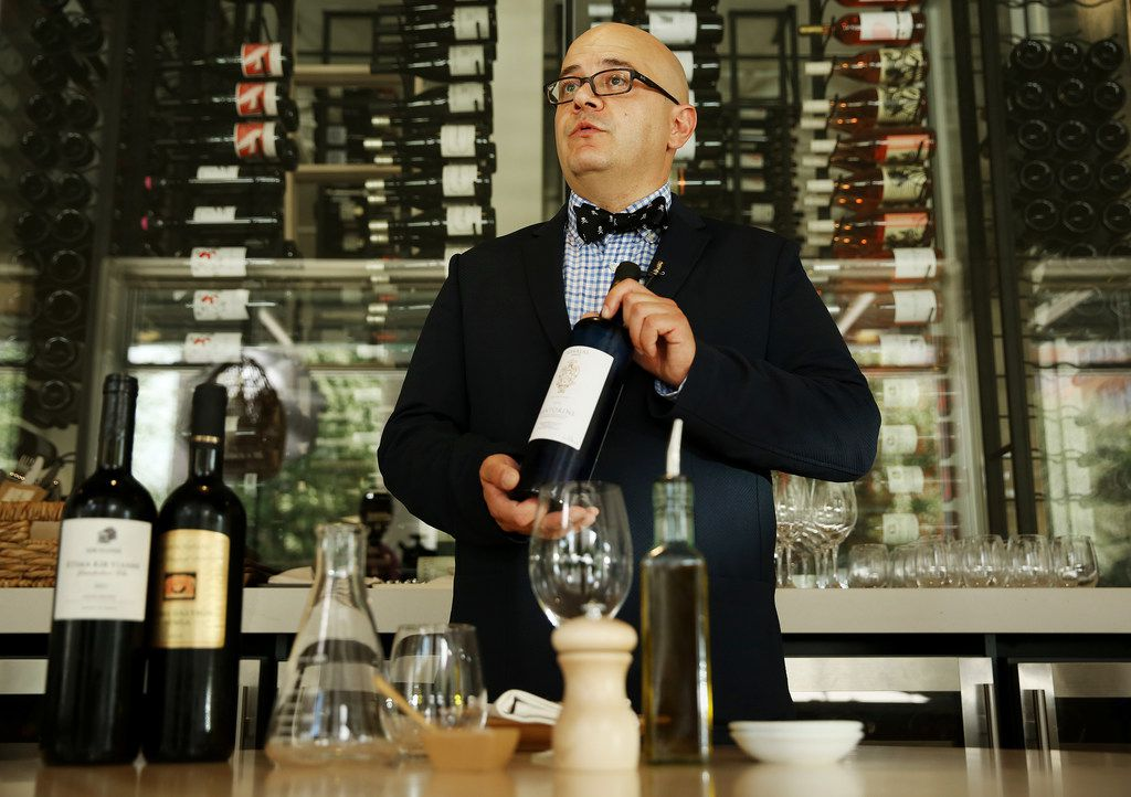 Richard Patino, general manager and wine director of Sachet restaurant, holds a bottle of Assyrtiko wine.