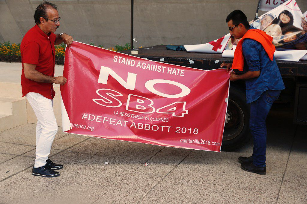 Carlos Quintanilla, left, and Francisco Salinas prepare to roll up a anti SB4 banner used at a rally against SB4 held at Dallas City Hall Sunday May 14,2017.  (Ron Baselice/The Dallas Morning News)