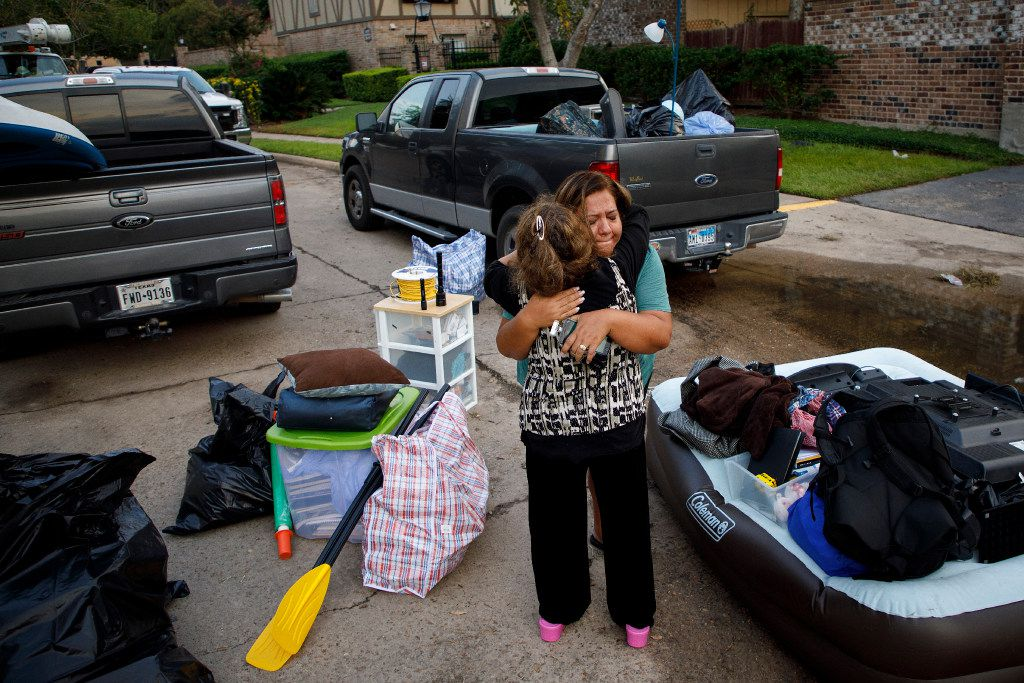 Dinah Moor (facing camera) hugs a resident of a west Houston apartment complex after she and her husband helped a couple check on their homes and retrieve belonging on Sunday, Sept. 3, 2017, in Houston.  The area remains flooded from Hurricane Harvey.