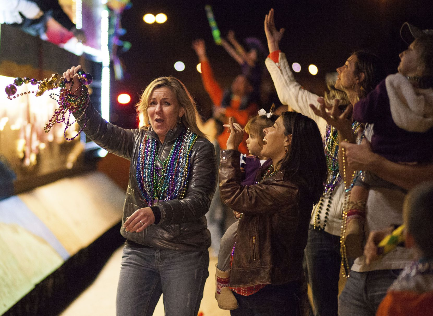 A woman celebrates her bead haul at the Krewe of Centaur parade in Shreveport.