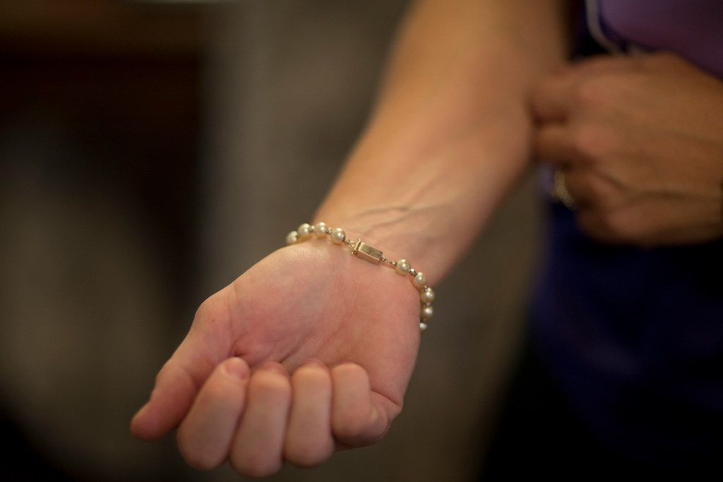 Penny Howard wears a bracelet that contains some of the ashes from her late daughter, Harper. (Ting Shen/The Dallas Morning News)