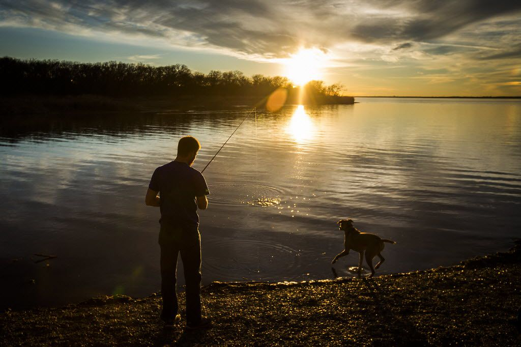 William Christie casts a line as he fishes with his dog at Joe Pool Lake