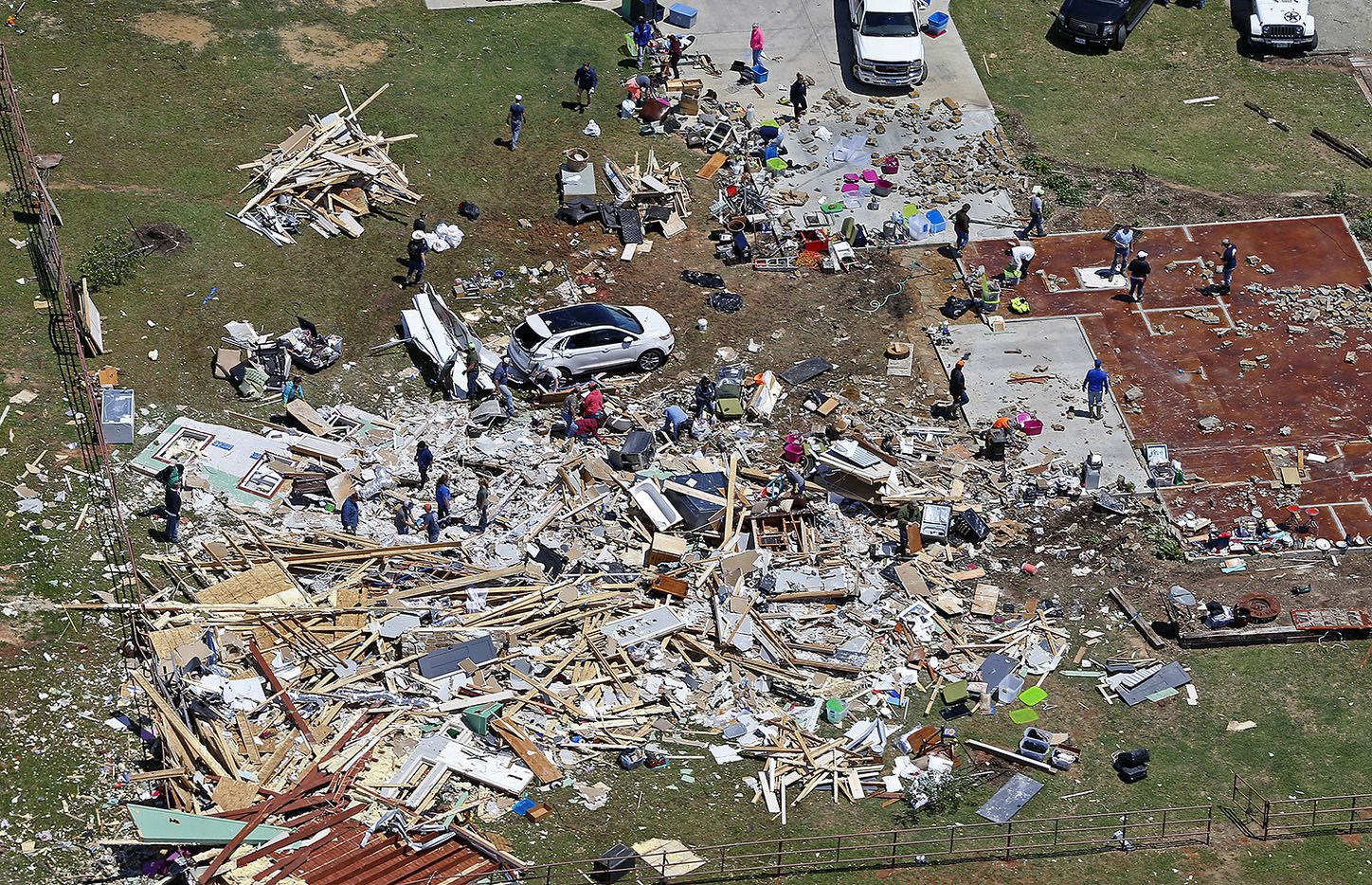 People clean up the debris at a house destroyed by yesterday's tornado in Canton, Texas, Sunday, April 30, 2017.