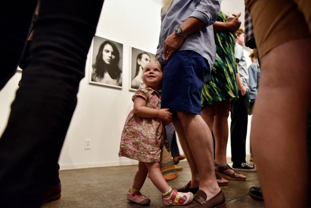 Matilda Smith, 2, hugs her dad Jon Paul Smith as the family mingled during opening night of Fredrik Broden's exhibit.