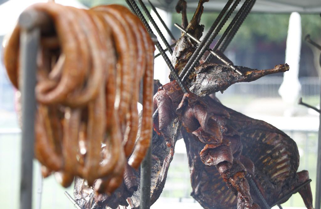 Meats are smoked on an open fire pit at the tent of Live Fire Pit with chef Tim Byres during the Fork & Cork festival Addison Circle Park in Addison, TX on May 15, 2015.
