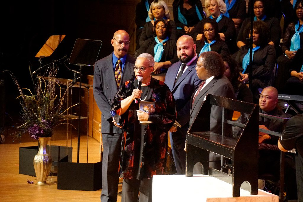 """Guy Davis and Nora Davis, the son and daughter of acting greats Ossie Davis and Ruby Dee, and grandson Jihad Muhammad present The Black Academy of Arts and Letters founder Curtis King with a bench owned by their parents during the """"Black Music and the Civil Rights Movement Concert"""" at the Morton H. Meyerson Symphony Center in Dallas on Sunday, Jan. 14, 2018."""
