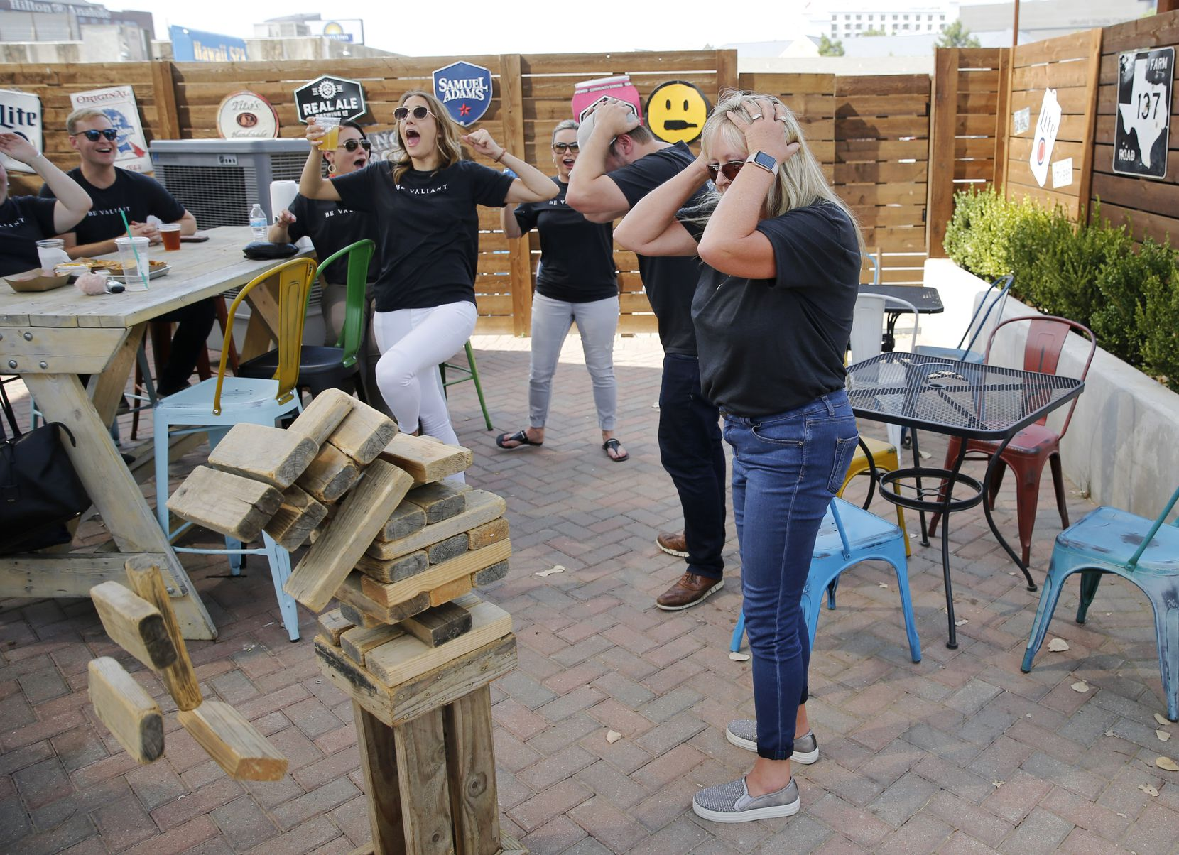 Kim Espinoza (right) and Craig Lashley (second from right) were dejected as Tanya Morales (center) and Emily Schroeder (in white pants) celebrated their victory in a game of Jenga during an employee appreciation event for Valiant Residential employees.