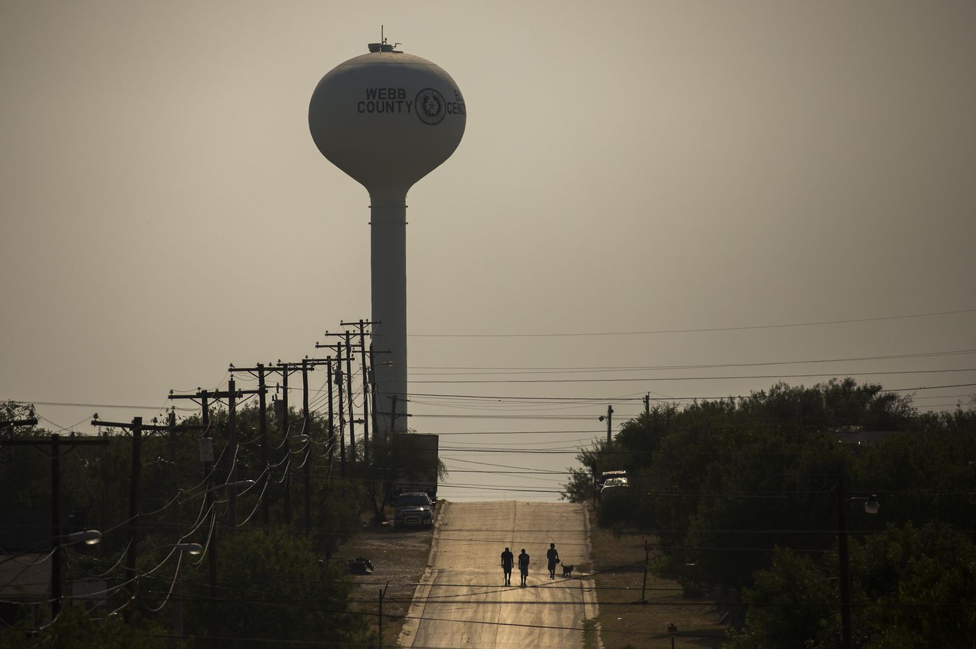 A group of young men walk along Valdez Street toward the town's water tower on May 10, 2017, in El Cenizo, Texas.