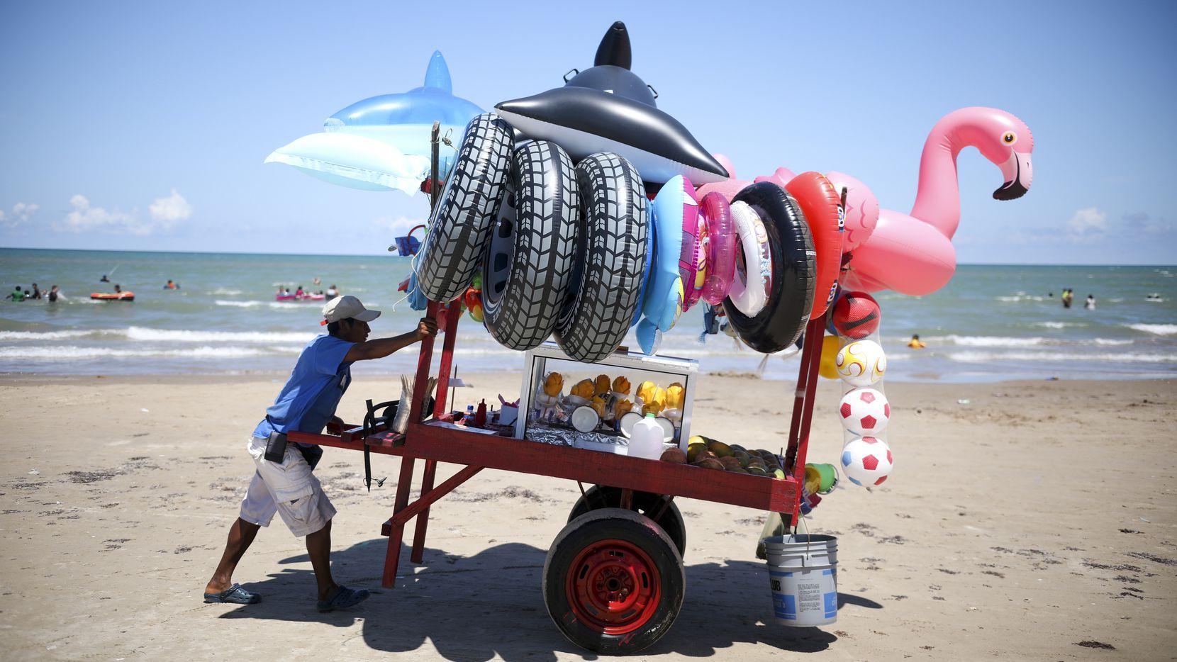 Un vendedor de juguetes inflables para la playa empuja su carrito en Playa Bagdad, Tamaulipas.