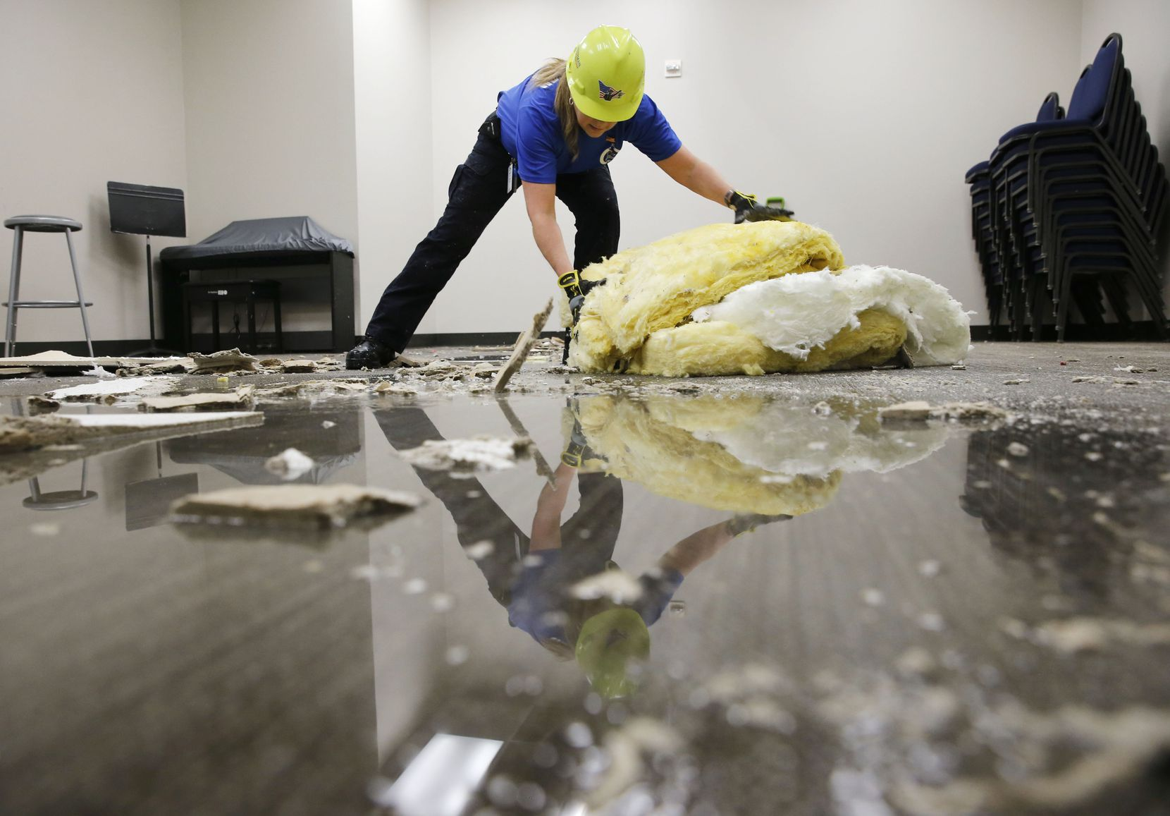 As water pools on the floor, Lisa Martin of Allen, a volunteer with the Minuteman Disaster Response Crew, worked Monday to clean up the student ministry area of Cottonwood Creek Church in Allen.