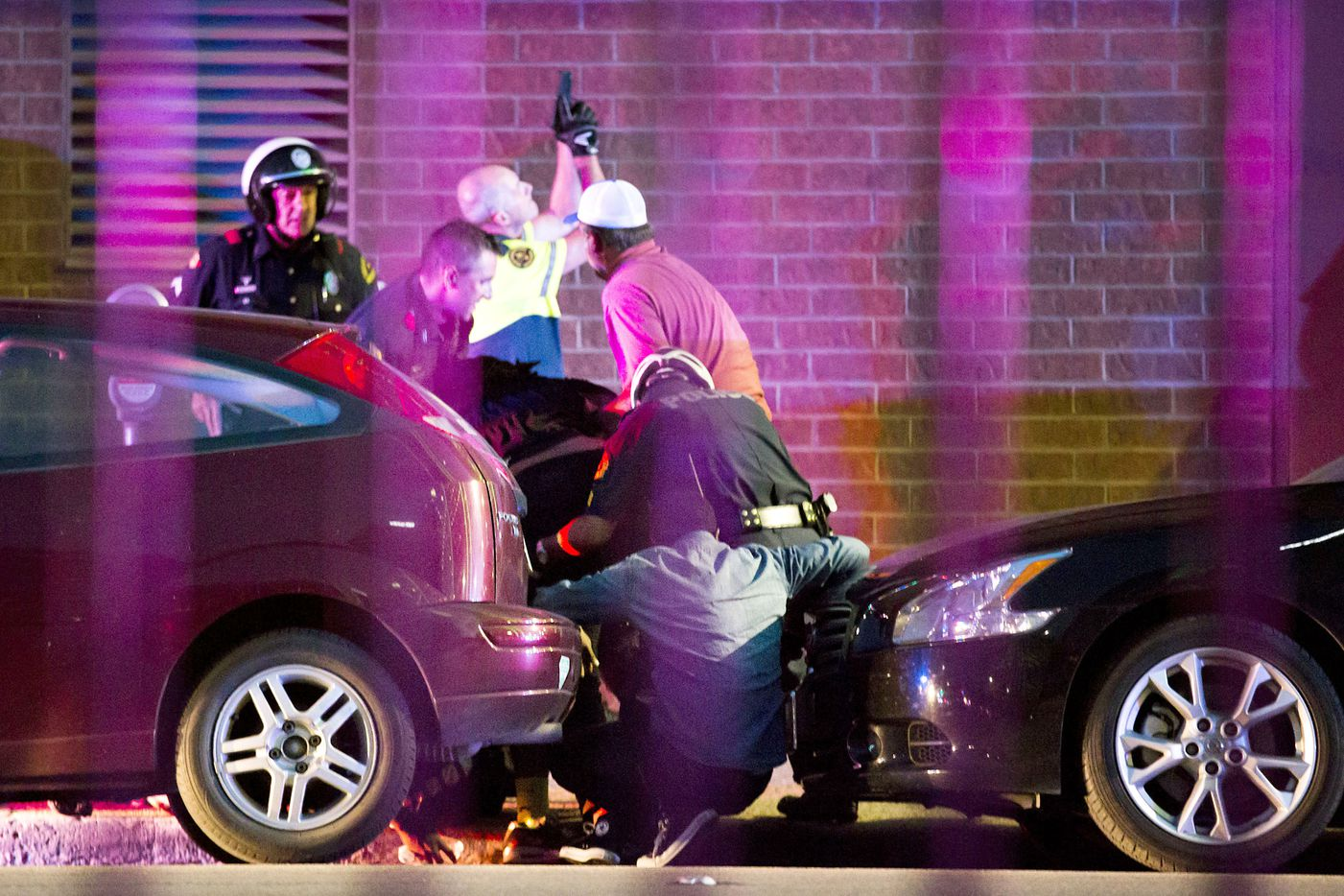 Shetamia Taylor (hunched over, in dark shirt, center), who was shot in the leg, is helped by several officers as they shield civilians and evacuate them from a position between two parked cars on Lamar Street between Main and Commerce at 9:02 p.m., minutes after the first shots were fired.