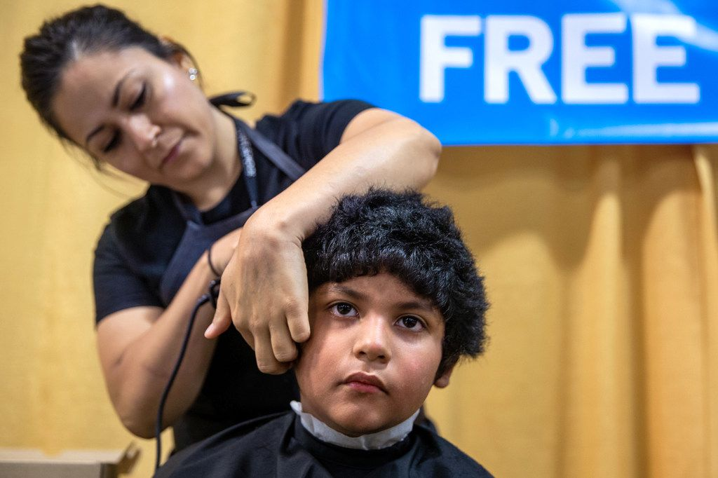 Jacob Lopez, 8 (right), receives a free haircut from Sharon Garcia during the 23rd annual Mayor's Back to School Fair at the Fair Park Centennial Hall in Dallas on Friday, Aug. 2, 2019. Thousands of children and their family members were expected to attend, and the event included health and eye screenings, dental screenings, backpack giveaways and more.