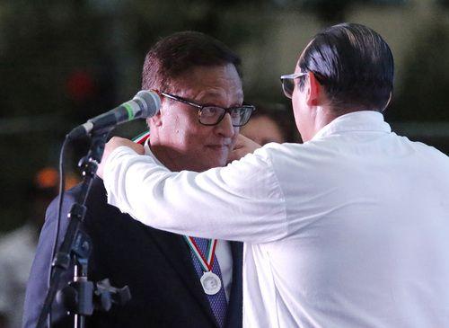 Jorge Baldor recibe el reconocimiento Ohtli por parte del consul general de México Francisco de la Torre, el sábado en el Main Street Park del centro de Dallas.