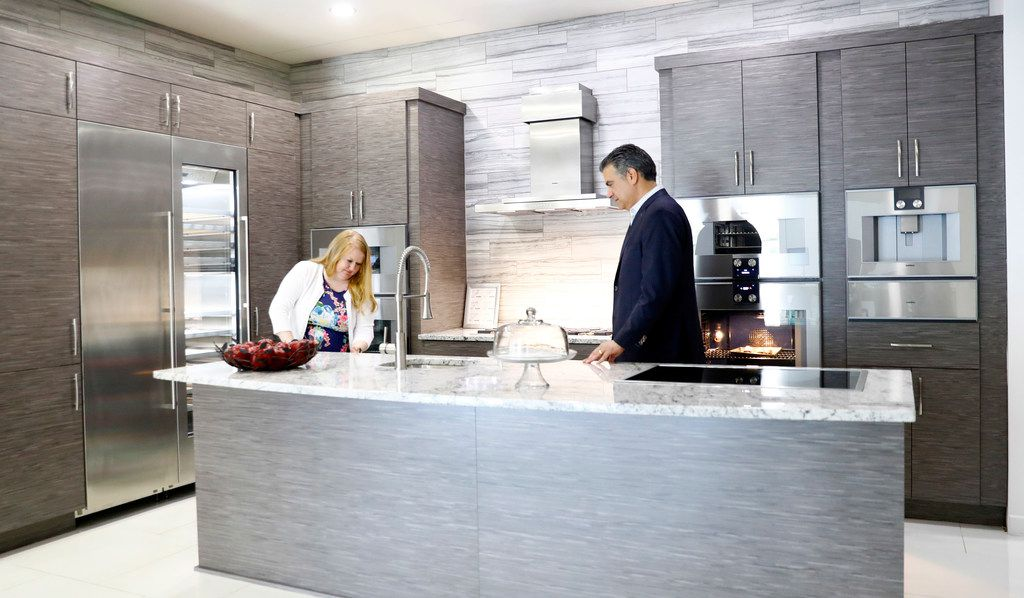 President Donald Trump's tariffs are already beginning to affect prices on appliances, including those made by Gaggenau, at Starpower in North Dallas. Starpower's Daniel Pidgeon (right) and Brandi Thompson test out Gaggenau appliances in one of their kitchens on Friday, July 13, 2018.