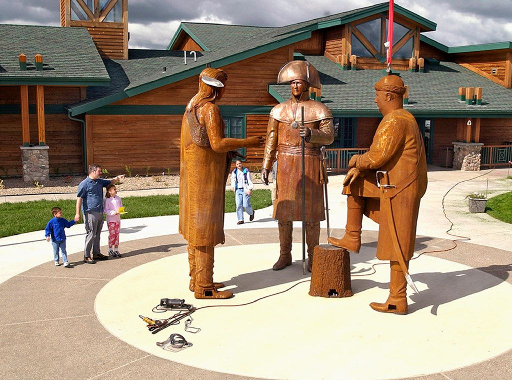 In this June 21, 2004 file photo, visitors walk past the figures of Chief Sheheke, left, Meriwether Lewis, center, and William Clark being installed in front of the Lewis and Clark Interpretive Center in Washburn, N.D. On Wednesday, May 24, 2017, a foundation announced it has transferred a nearly $700,000 endowment trust to support maintenance at the center. The state took over the center's operations from the financially troubled foundation two years ago. (Tom Stromme/The Bismarck Tribune via AP, File)