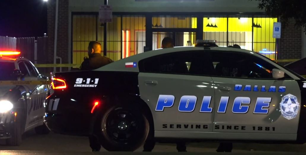 Dallas police officers stand outside a business near were a shooting victim was found Friday morning in South Dallas.
