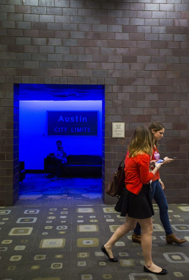 Women walk past while Ben Pickup of Washington DC talks to his daughters on a cell phone in a glowing Austin City Limits artist lounge.