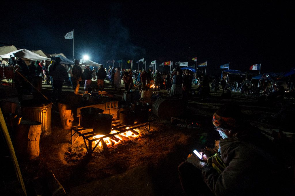 People gathering at the Sacred fire at the Oceti Sakowin Camp in North Dakota on Wednesday, Sep 14th, 2016.  At the centre of the Red Warrior Camp is a microphone, and at night, a blazing fire. Anyone can stand up and speak or sing. Construction has been halted after the Obama administration decision to suspend construction on a controversial oil pipeline in North Dakota.  (Jeenah Moon/Special Contributor)