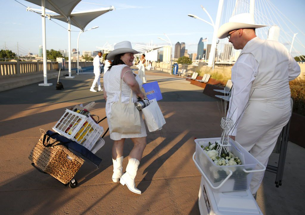 Donna VanderGrinten and Jim Michalek carry food, chairs and a centerpiece for the inaugural Diner en Blanc Dallas on the Continental Avenue Bridge in Dallas on Sept. 17, 2015. Exactly 1,678 people attended the event, which requires dinner guests to dress all in white and bring their own tables, chairs and centerpieces. As per tradition, the location was kept private leading up to the event.