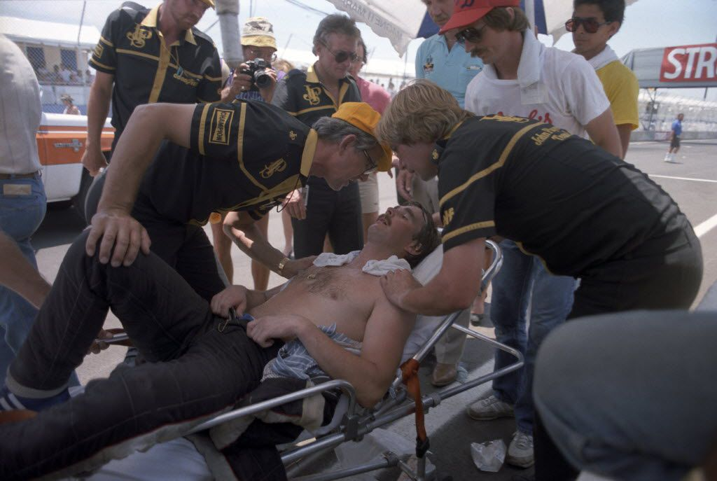 Driver Nigel Mansell is attended to after pushing his car at the end of the 1984 Formula One Grand Prix championship race at Fair Park in Dallas.