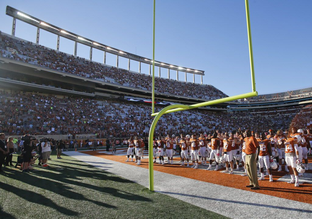 """The Texas Longhorns stand in the end zone for the """"Eyes of Texas"""" rendition before going to the locker room after their 28-7 loss during the Baylor University Bears vs. the University of Texas Longhorns NCAA football game at Darrell K. Royal-Texas Memorial Stadium in Austin on Saturday, October 4, 2014.  (Louis DeLuca/The Dallas Morning News)"""