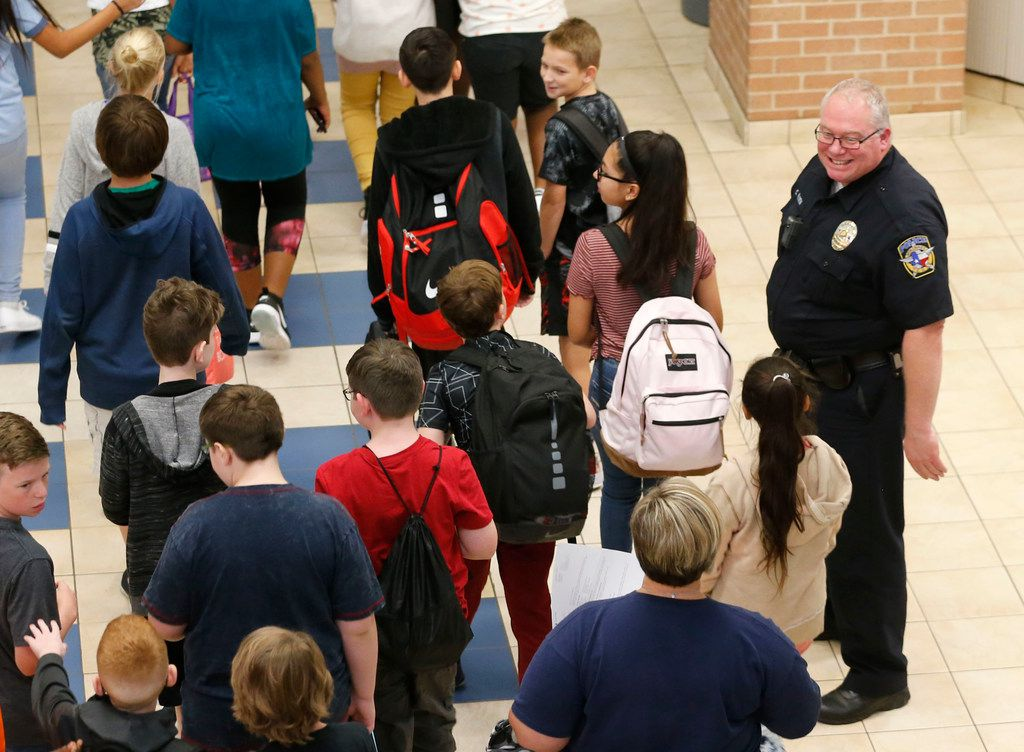 McKinney police school resource officer Chris Golden smiles at students as they make their way to the cafeteria at Scott Johnson Middle School in McKinney on Thursday. (Vernon Bryant/The Dallas Morning News)