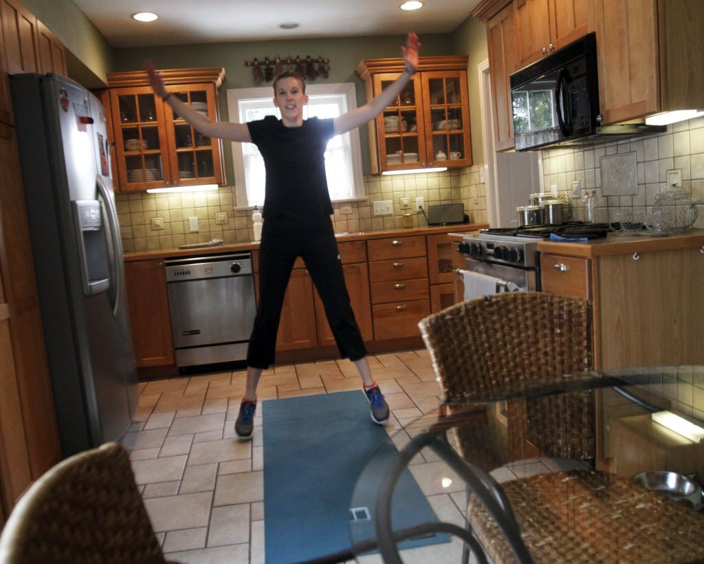 Personal trainer Lori Louis is all about the jumping jacks, which she demonstrates in her kitchen in this file photo. Five minutes — you have time! Who knows what that could lead to.