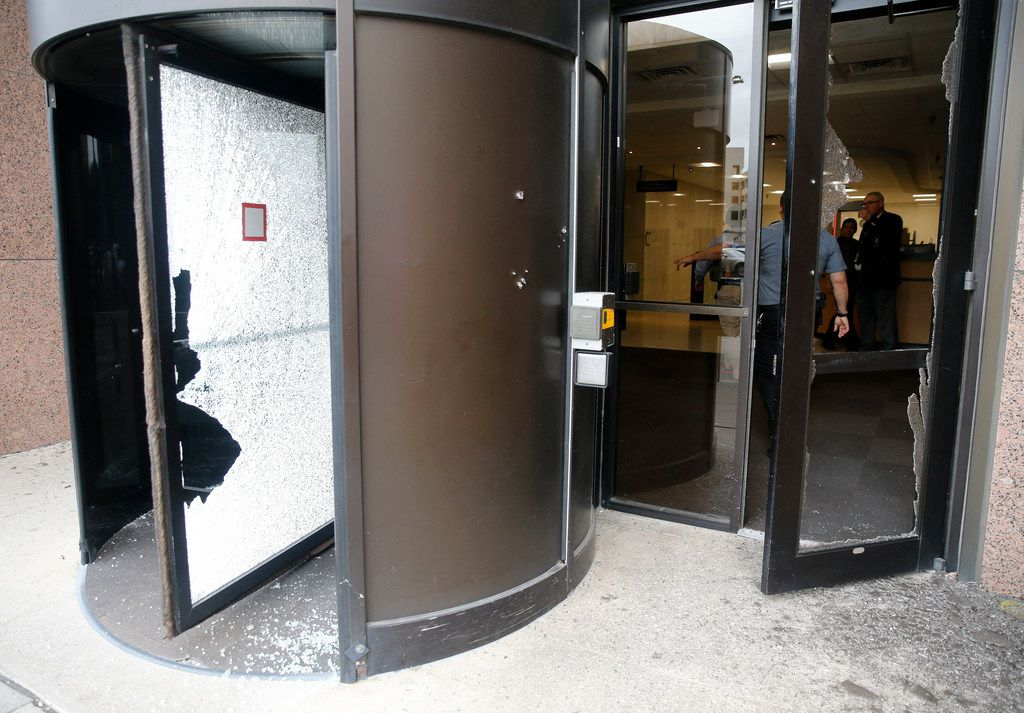 Shattered glass in the entry doors after shots were fired Monday morning, June 17, 2019 at the Earle Cabell federal courthouse in downtown Dallas. Law enforcement returned fire and the shooter was hit by gunfire. No officers or citizens were injured. (Tom Fox/The Dallas Morning News)  -- MANDATORY CREDIT; NO SALES; MAGS OUT; TV OUT; INTERNET USE BY AP MEMBERS ONLY