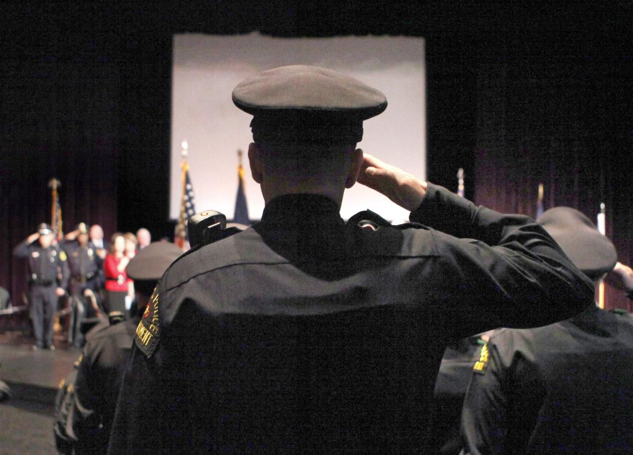 Graduates salute during a ceremony for a Dallas Police Department Basic Academy recruit class. This year's application numbers are on pace to exceed last year's.