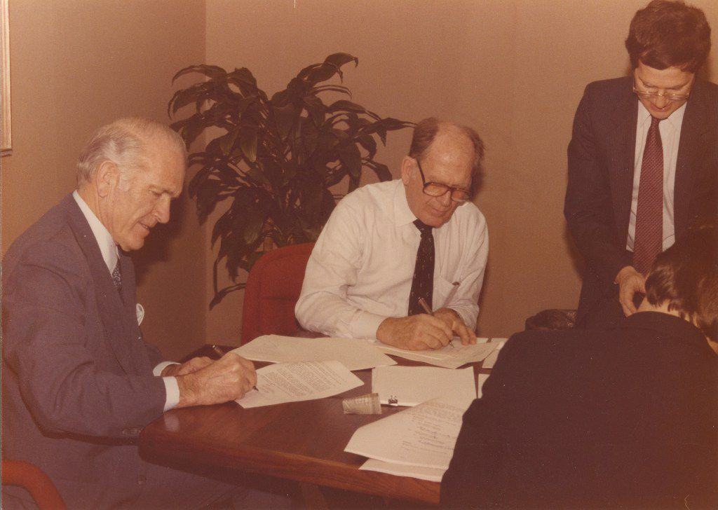 Frequent business partners Cloyce Box (left) and Trammell Crow (right) sign documents.