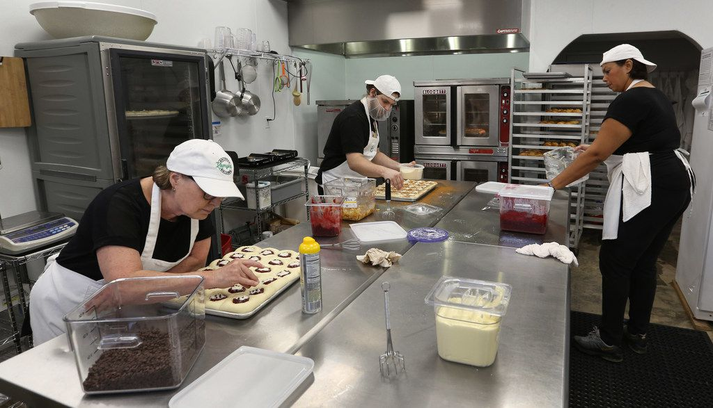 In the kitchen, executive baker Judé Routh (left) and the staff stay busy making kolaches at Zamykal Gourmet Kolaches on Keller Springs Road. They make 600 kolaches a day — or 900 on busy days. (Louis DeLuca/Staff Photographer)
