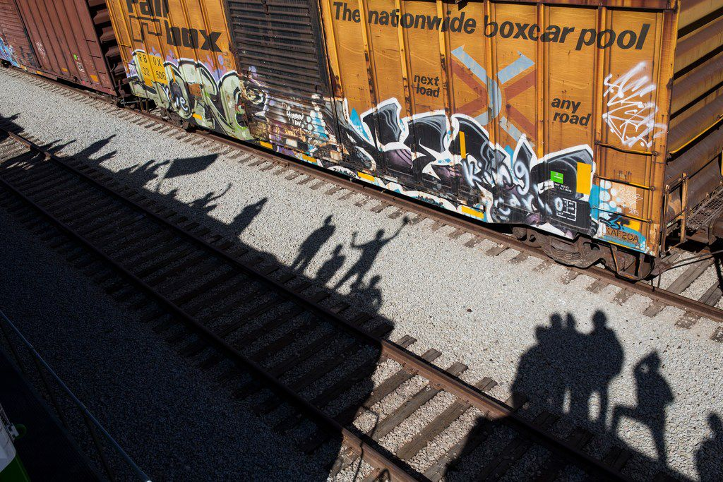 Shadows of migrants are cast on the railroad tracks at the Mexico-U.S. border in Tijuana, Mexico, Sunday, Nov. 25, 2018, as a group of migrants tries to reach the U.S. The mayor of Tijuana has declared a humanitarian crisis in his border city and says that he has asked the United Nations for aid to deal with the approximately 5,000 Central American migrants who have arrived in the city. (AP Photo/Rodrigo Abd)