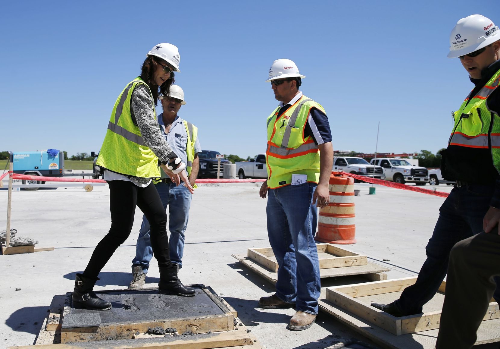 Charlotte Jones Anderson (left) Executive Vice President and Chief Brand Officer for the Dallas Cowboys attempts to replicate the stance of Roger Staubach as Andrew Pipkin, Superintendent at Metric Concrete, Brian Bethea (center, right), and Project Director Nicholas Link (far right), of Manhattan Construction Company watch in preparation for a foot imprinted Staubach and Drew Pearson press conference the next day at the Dallas Cowboys new headquarters at The Star in Frisco, on Tuesday, May 3, 2016. The Star a joint project with the City of Frisco is scheduled to open in August. (Vernon Bryant/The Dallas Morning News)