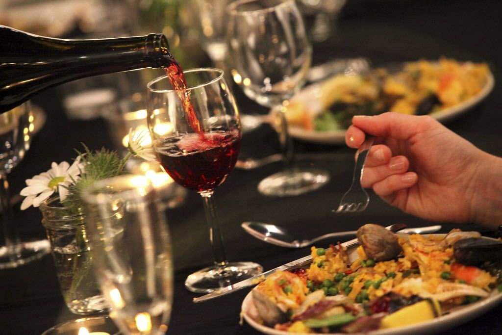 Wine is served as guests dine on Paella made by guest chef/artist Jason Willaford.