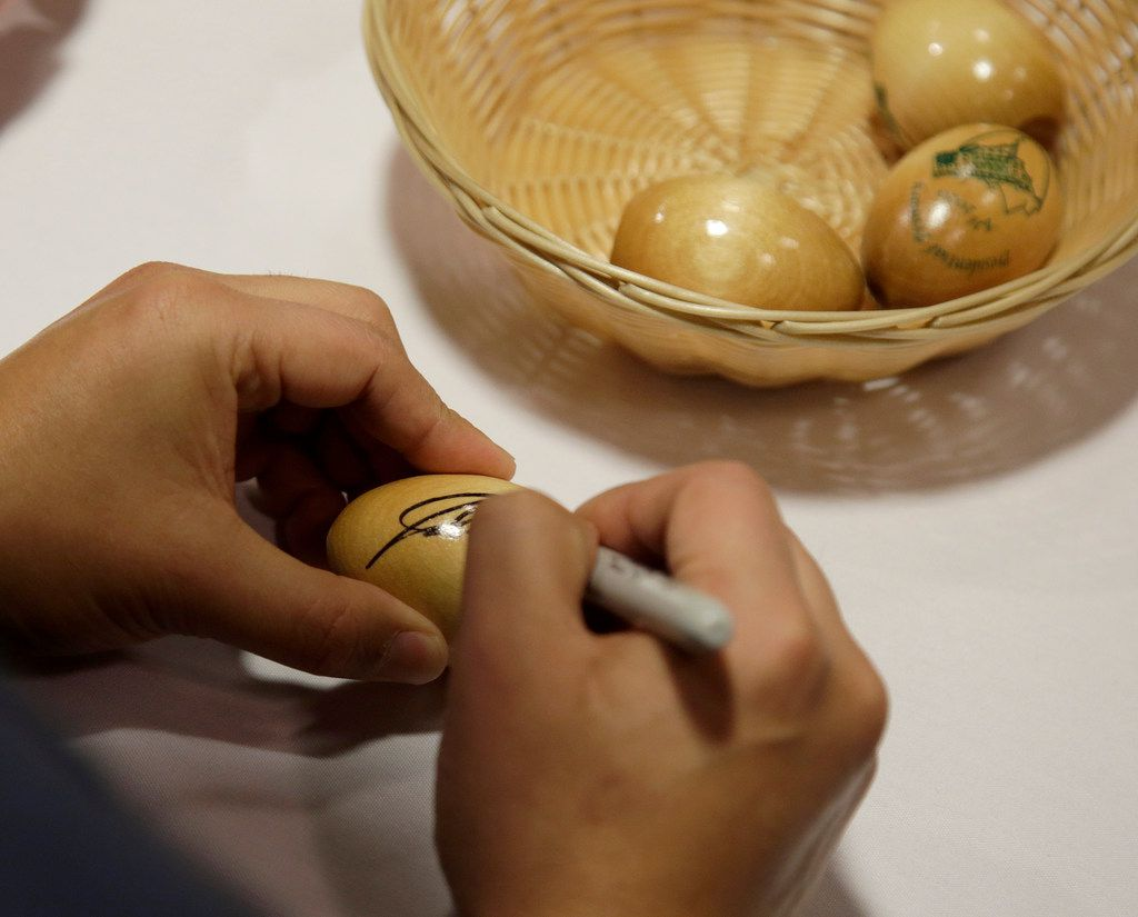 Julian Castro, former U.S. Secretary of Housing and Urban Development and candidate for the 2020 Democratic presidential nomination, signs wooden eggs before speaking at Saint Anselm College, Wednesday, Jan. 16, 2019, in Manchester, N.H.