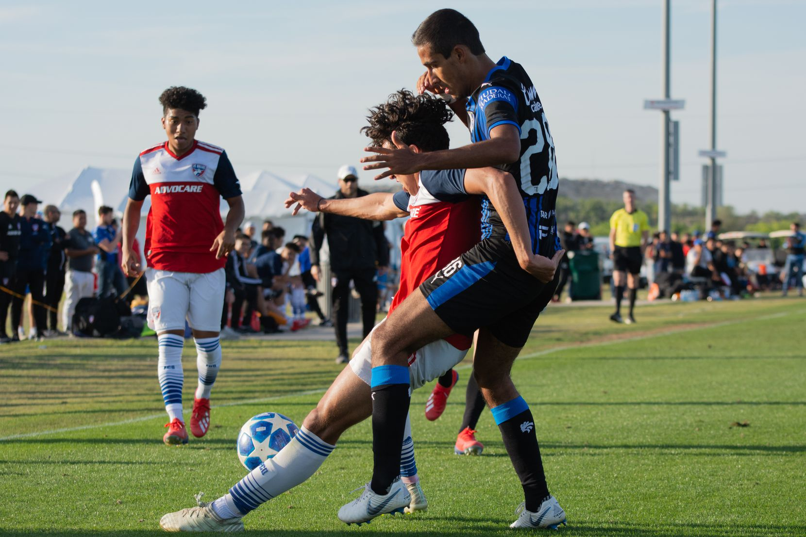 Johan Gomez shield off a Queretaro defender in the 2019 Dallas Cup Super Group at MoneyGram Park.  Kevin Bonilla looks on in the background.