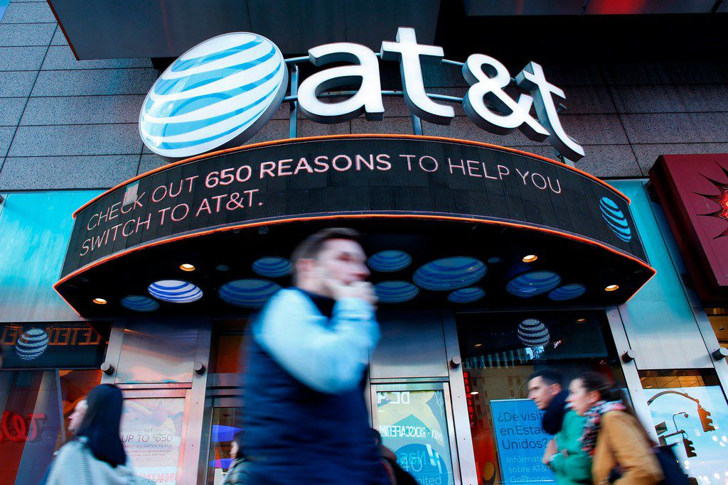 People walk past an AT&T store in New York in 2016