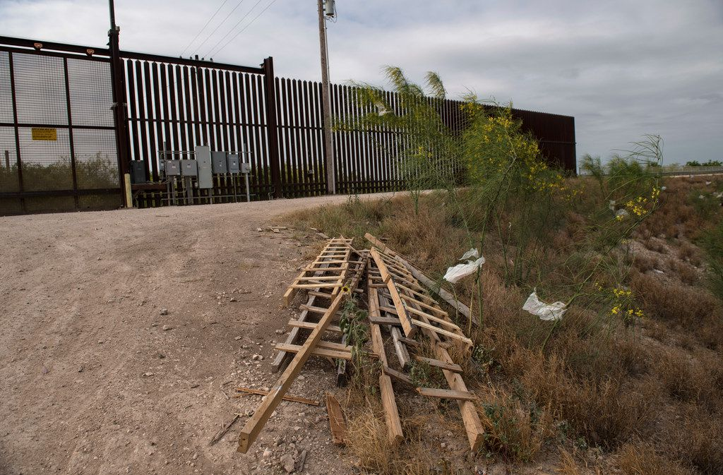Ladders used by immigrants to scale walls and levees sit by the border fence near McAllen, Texas.