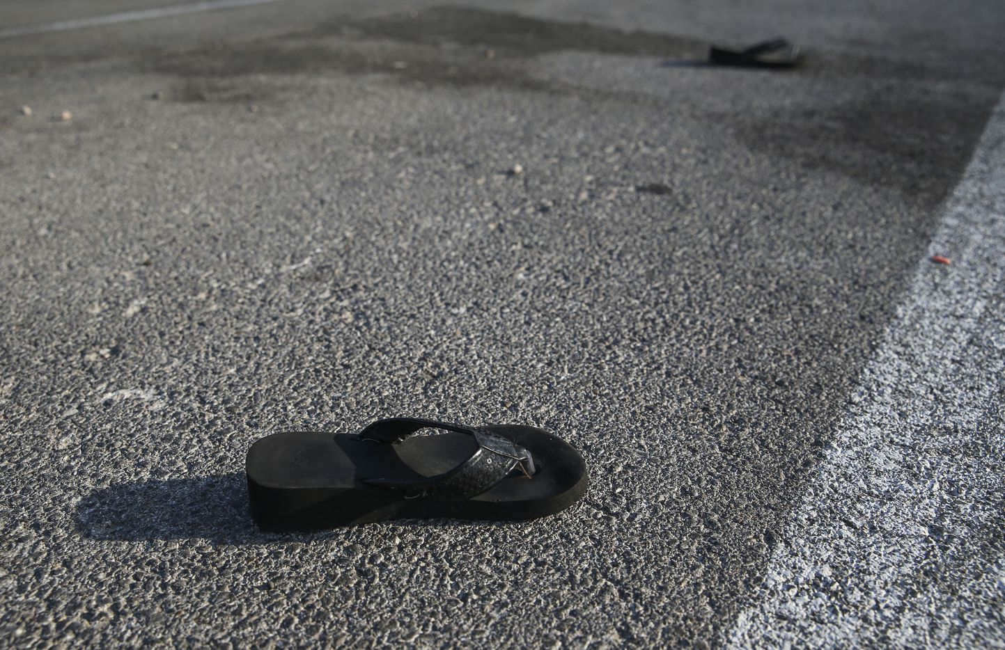A pair of lost sandals are seen Sunday, Sept. 1, 2019 in the parking lot of the Odessa, Texas Cinergy movie theatre where police took down a gunman Saturday.