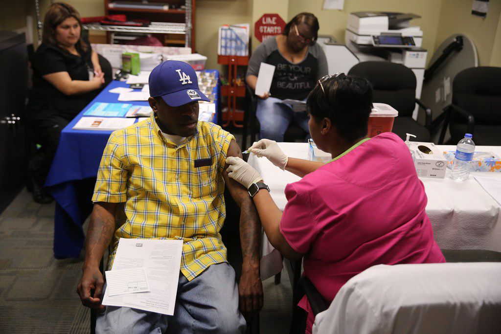 Daniel Robertson of Dallas receives the flu vaccine Tuesday from Barbara Davis at a mobile immunization clinic hosted by Dallas County Health and Human Services at the DeSoto Senior Center.