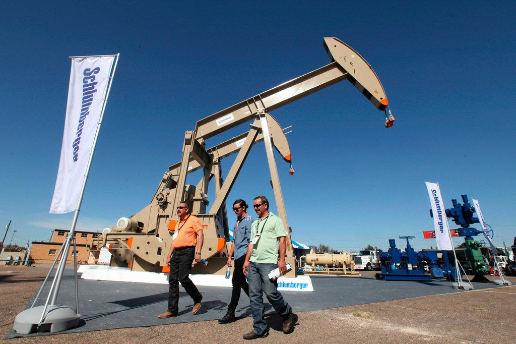 FILE - In this Oct. 18, 2016, file photo, oil show attendees walk past the Schlumberger booth at the Permian Basin International Oil Show at Ector County Coliseum, in Odessa, Texas. Schlumberger N.V. reports earnings Friday, April 20, 2018. (Jacob Ford/Odessa American via AP, File)