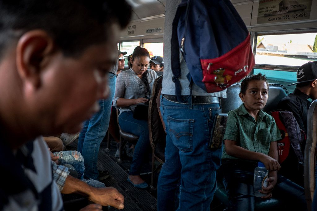 Edgar Yovani Monjel, 34, far left, and his son Cristopher, 7, right, ride a bus from a migrant shelter in Juarez to downtown where they will then walk to a U.S. Port of Entry on Thursday, Aug. 1, 2019. The Monjel family was headed to immigration court.Protocols program.  (Joel Angel Juarez/Special Contributor)
