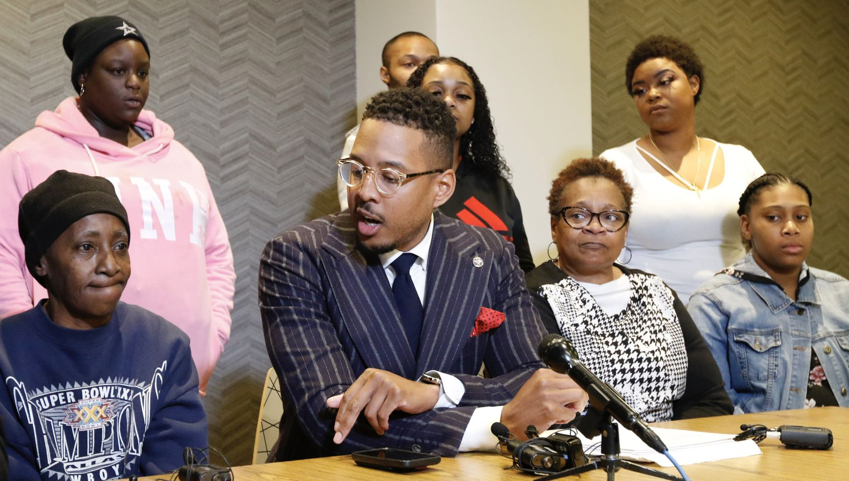 "Ethelyn Ross, left, mother of Diamond Ross, and other family members listen to attorney Justin Moore, center, talk about the video on Friday morning, Nov. 8, 2019 in Dallas, Texas. Dallas police released ""disturbing"" videos late Wednesday that show the final hours of Ross, a 34-year-old woman who died in police custody of an overdose in 2018."