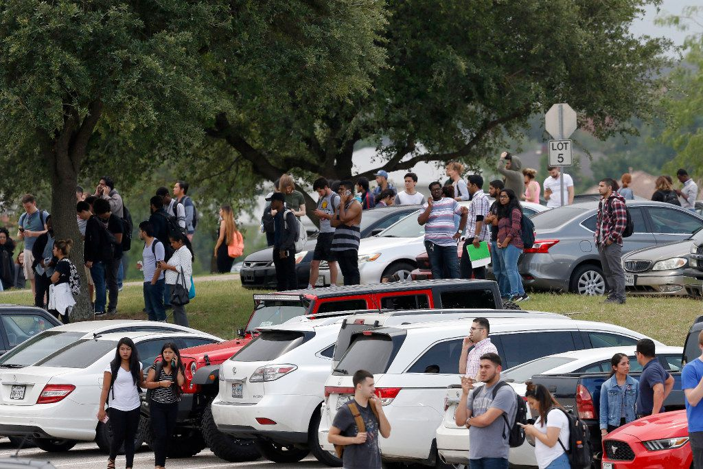 People stand in the parking lot at the North Lake College campus in Irving.