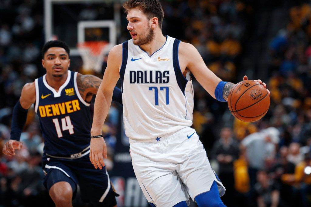 Dallas Mavericks forward Luka Doncic, front, drives as Denver Nuggets guard Gary Harris defends during the first half of an NBA basketball game Thursday, March 14, 2019, in Denver. (AP Photo/David Zalubowski)