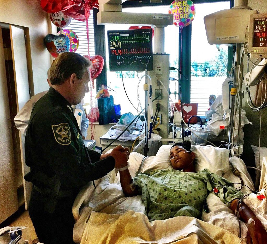 En esta foto del 18 de febrero de 2018, el jefe de policía del condado Broward, Scott Israel, sostiene la mano de Anthony Borges, un estudiante venezolano herido en el tiroteo del 14 de febrero en la escuela secundaria Stoneman Douglas. (Broward County Sheriff's Office via AP)